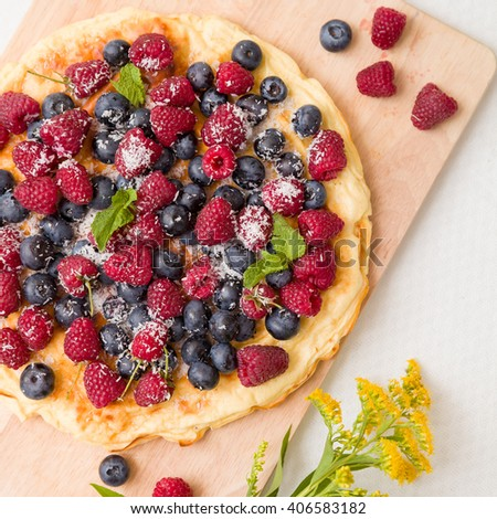 Fresh berries on the tart cake from above. Delicious homemade pie with organic raspberries and blueberries and summer flowers on wooden board. Summer dessert and snack. - stock photo
