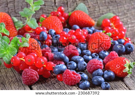 Fresh berries with mint leaves on a wooden background