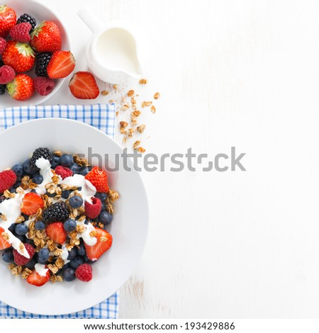 fresh berries, yogurt and homemade granola for breakfast and space for text, top view - stock photo