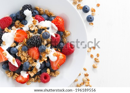 fresh berries, yogurt and homemade granola for breakfast, close-up, top view, horizontal - stock photo