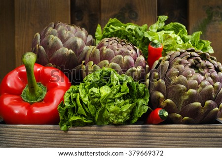 Fresh big Romanesco artichokes green-purple flower heads, red paprika, romanine lettuce on wooden background