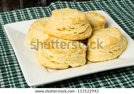 Fresh biscuits or scones on a white plate with cloth