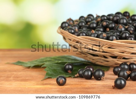 Fresh black currant in wicker basket on green background close-up - stock photo