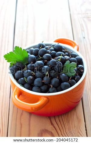 Fresh black gooseberries in orange ceramic bowl - stock photo