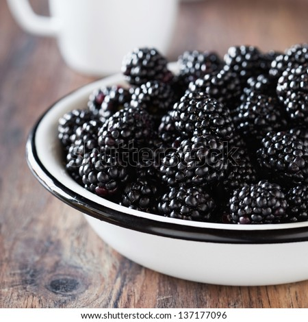 Fresh blackberries in metal bowl, selective focus - stock photo