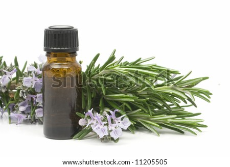 Fresh blossoming rosemary branch and a bottle of essential oil used for aroma therapy - stock photo