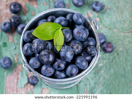fresh blueberries in a bucket on wooden surface - stock photo