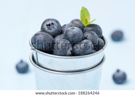 Fresh blueberries in a metal bucket, selective focus, close-up - stock photo