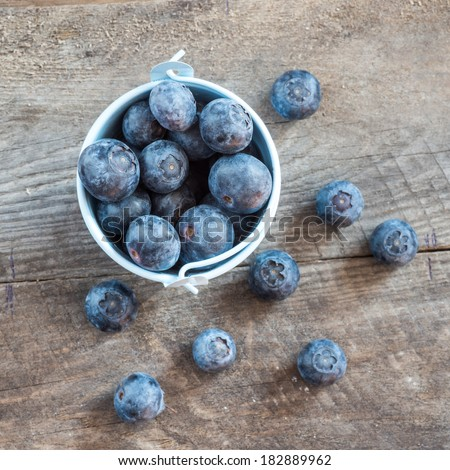 Fresh blueberries in white bowl on wood table, rustic style - stock photo