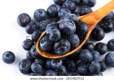 Fresh blueberries in wooden spoon on white background - stock photo