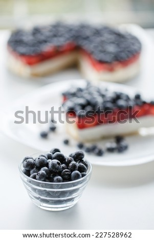 Fresh blueberries on white table, selective focus. blueberry pie on background. - stock photo