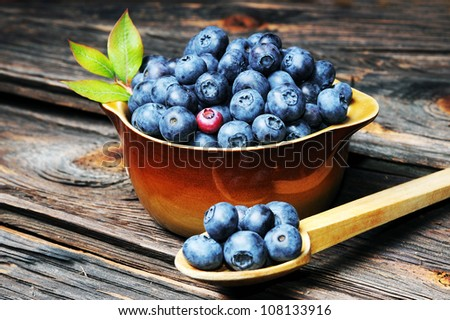 Fresh blueberries spilling from vintage wooden spoon onto wood table. - stock photo