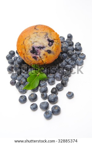 Fresh blueberries surround a single blueberry muffin on a light background - stock photo