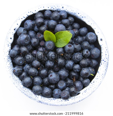 Fresh blueberries with leaves in the  bowl on white background - stock photo