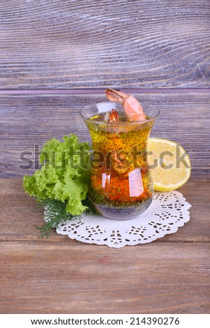 Fresh boiled prawns with lettuce and lemon in a glass of sauce on a lace napkin on wooden background - stock photo