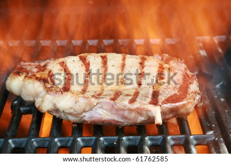 Fresh Boneless Rib-eye steak cooking on a barbecue with flames and smoke