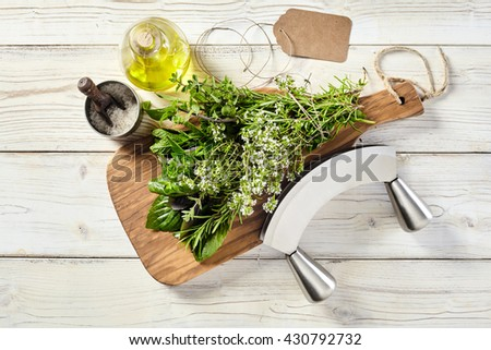 Fresh bouquet garni of assorted potherbs tied in a bunch on a chopping board with a mezzaluna knife, salt and olive oil on a white wooden table, overhead view - stock photo