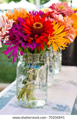 Fresh bouquets displayed in jars - stock photo