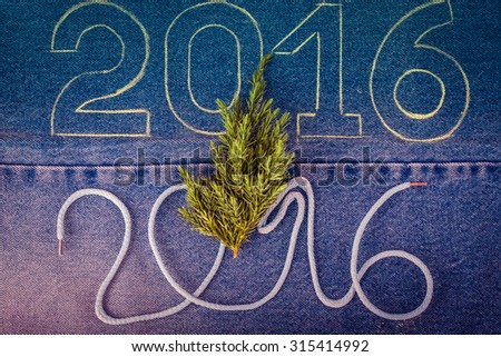 Fresh branch of christmas tree and the numbers 2016 of rope and chalk contour on the background of the jeans. Christmas theme. Toned. - stock photo