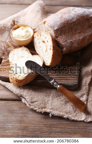 Fresh bread and homemade butter on wooden background - stock photo