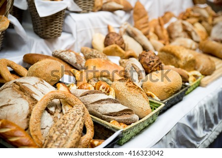 Fresh bread and pastry composed on the table - stock photo