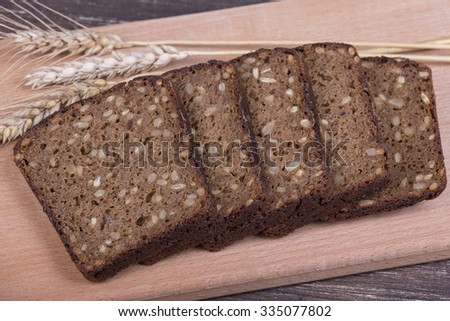 Fresh bread and wheat on the wooden, close up - stock photo