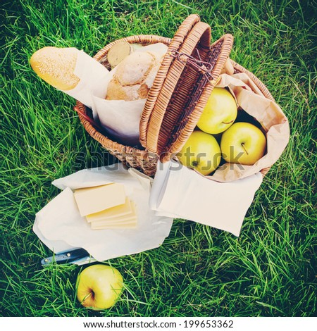 Fresh Bread, Apples, Cheese in a Wattled Basket on Green Grass, picnic - stock photo