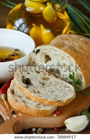 Fresh bread ciabatta and aromatic olive oil with herbs and spices. - stock photo