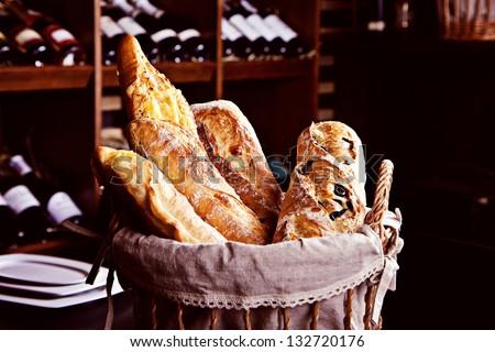 Fresh bread in basket witn bottles of wine on background - stock photo