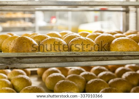 Fresh bread on cooling racks in an industrial kitchen - stock photo