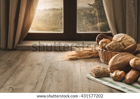 Fresh bread on the kitchen table in front of a window with a countryside panorama, healthy eating and traditional bakery concept - stock photo