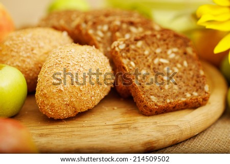 Fresh bread. Pieces of bread with sunflower seeds. Loaf of wholemeal bread and sliced  pieces are on the table. Apple, sunflower, pieces of bread, table, bun, corn - autumn concept advertising bread. - stock photo
