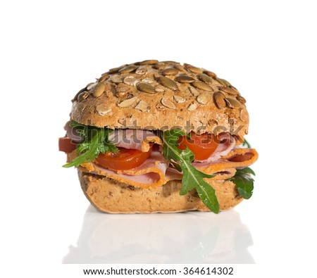 Fresh bread roll filled with ham, tomato and rocket salad - stock photo