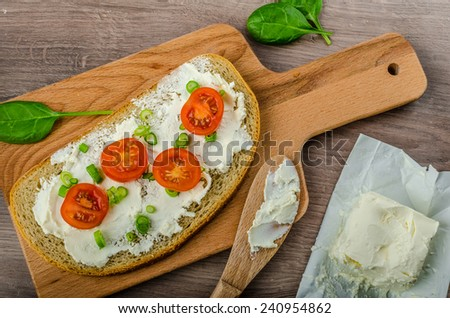 Fresh bread smeared with cream cheese, cherry tomatoes and spring onions, milk from farm - stock photo