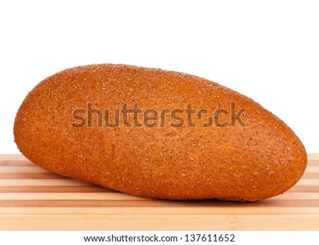 Fresh bread with bran on a cutting board on white background - stock photo