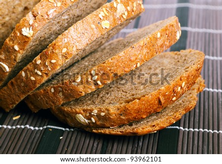 Fresh bread with bran on wooden placemat