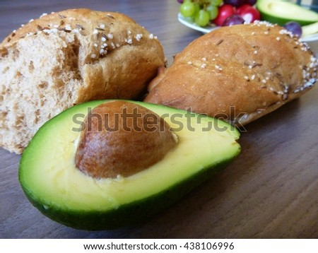 fresh bread with half of avocado on a wooden table - stock photo