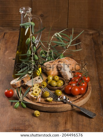 Fresh bread with olives, tomatoes and olive oil  on an old wooden board. - stock photo