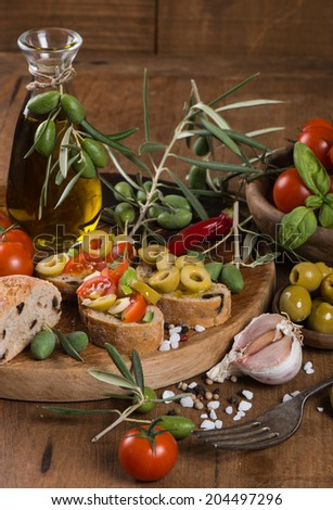 Fresh bread with olives, tomatoes, spices and olive oil on an old wooden board. - stock photo