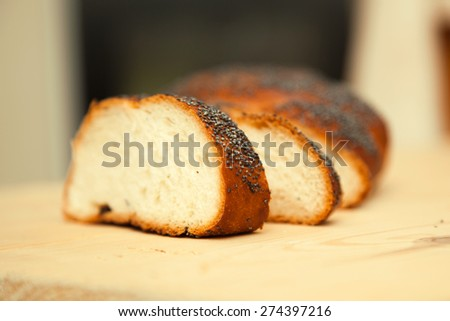 Fresh bread with poppy seeds on wooden table