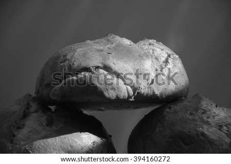 Fresh bread with raisins on red background. Contrast light and dark shadows. Black and white aged photo.  - stock photo