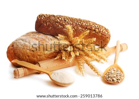 Fresh bread with wheat, flour and sunflower seeds in wooden spoons isolated on white - stock photo