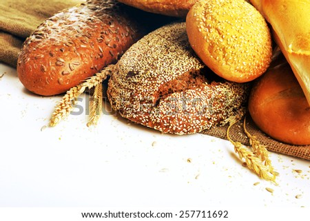 Fresh bread with wheat, sesame and sunflower seeds isolated on white