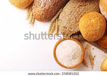 Fresh bread with wheat, sesame, sunflower seeds and wooden bowl of flour isolated on white