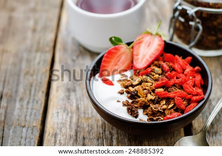 fresh breakfast of granola, yogurt, nuts, goji berries and strawberries. tinting. selective focus - stock photo