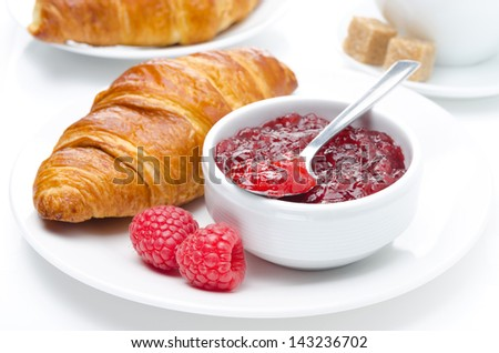 fresh breakfast - raspberry jam and croissant on a plate, isolated on white