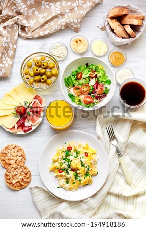 Fresh breakfast table. Healthy food. Top view. Scrambled eggs, salad, cheese, prosciutto, coffee and juice. Concept of business or holiday breakfast.  - stock photo