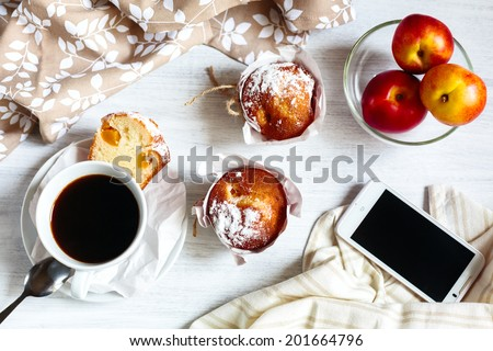 Fresh breakfast with muffins in paper cupcake holders, coffee and fruits (peach and nectarine). Phone for social media and morning news. - stock photo