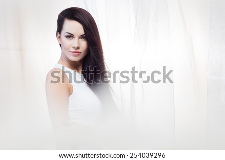 Fresh breeze is waving a piece of white silk fabric behind a beautiful young girl - stock photo