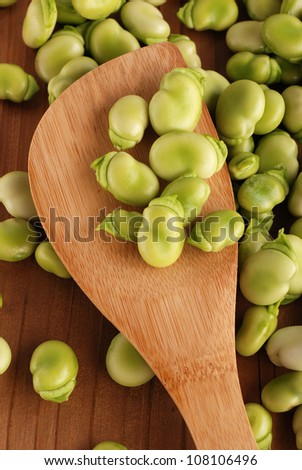 fresh broad beans on the wooden table - stock photo